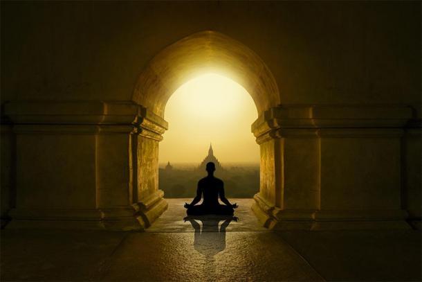Silhouette en train de méditer dans un temple bouddhiste. (tir rapide / stock Adobe)