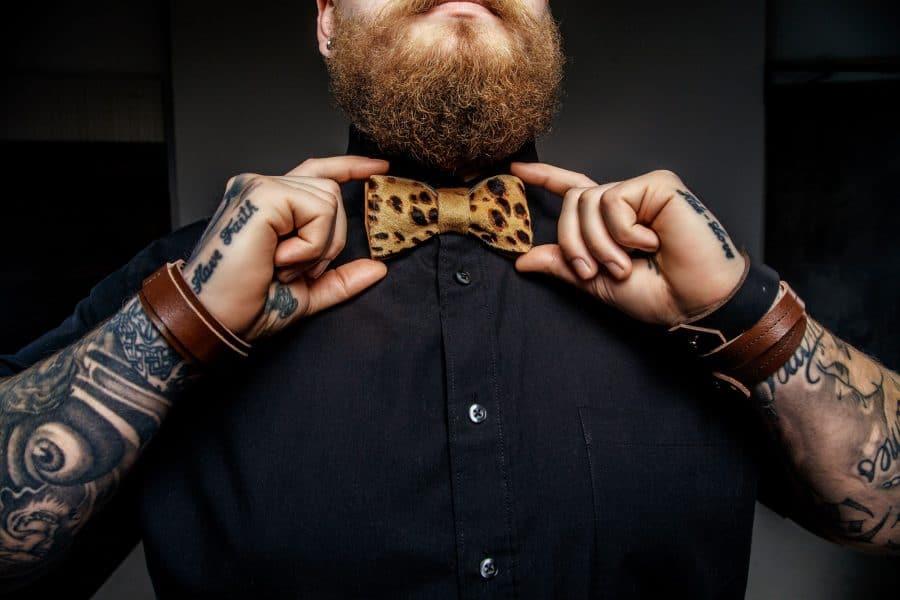 Un homme visiblement tatoué avec un nœud papillon