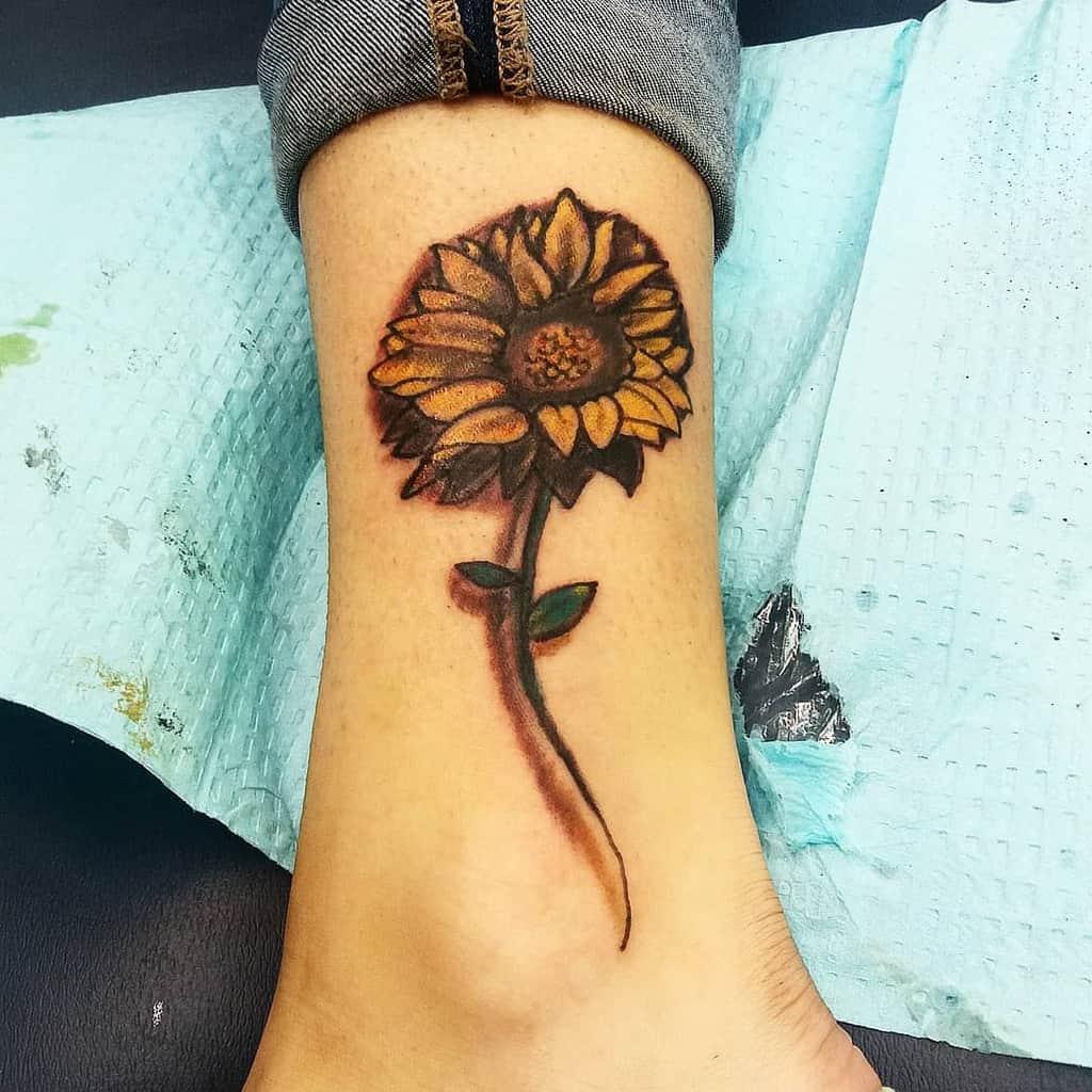 Petit tatouage de tournesol sur la cheville Mastermindstattoo