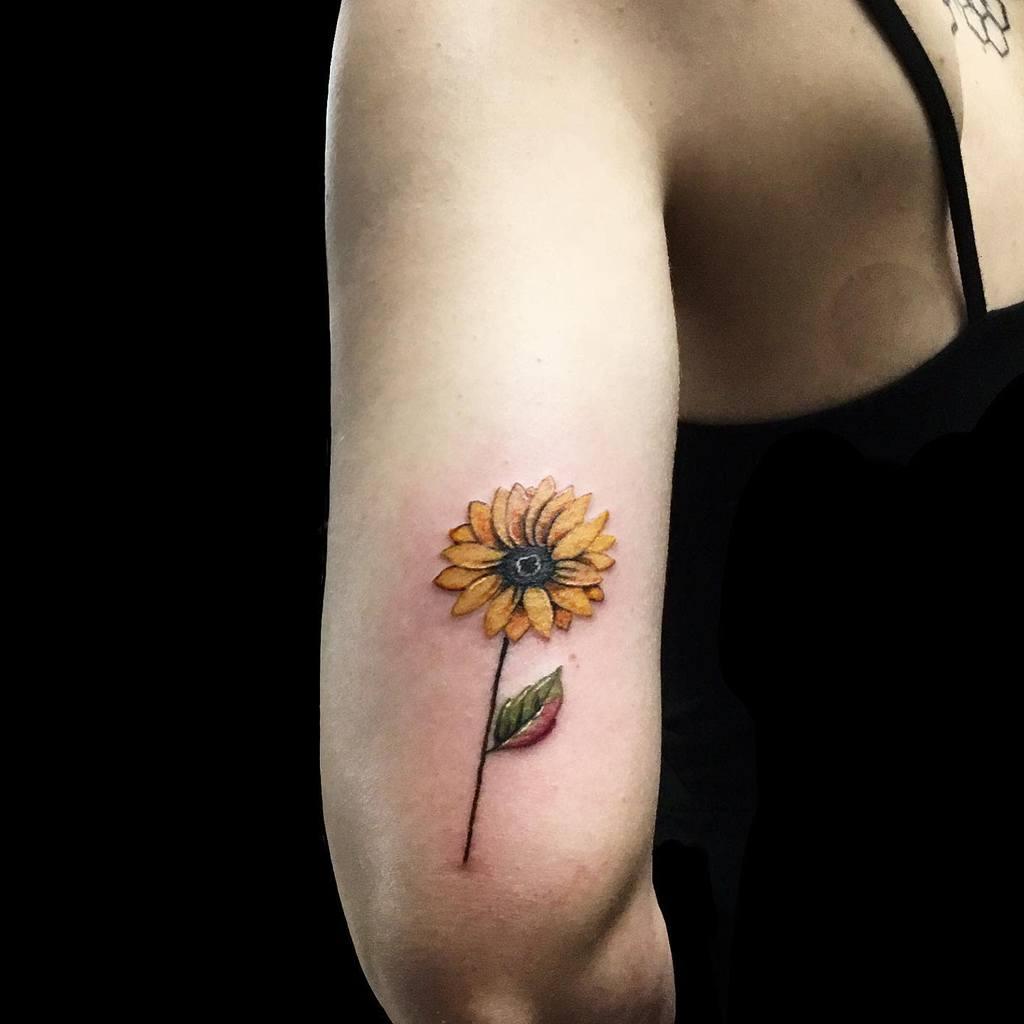 Tatouage à l'encre K sur un petit bras de tournesol
