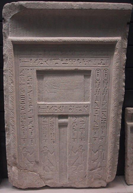 Une fausse porte typique d'un tombeau égyptien - le défunt est représenté au-dessus de la niche centrale devant une table d'offrandes, et des inscriptions énumérant les offrandes pour le défunt sont sculptées le long des panneaux latéraux. (CC BY SA 3.0)